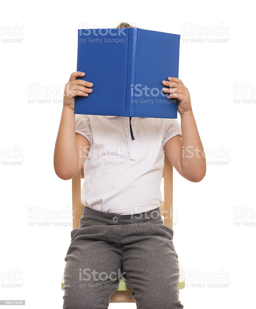 child sitting on a chair covered face with blue book foto