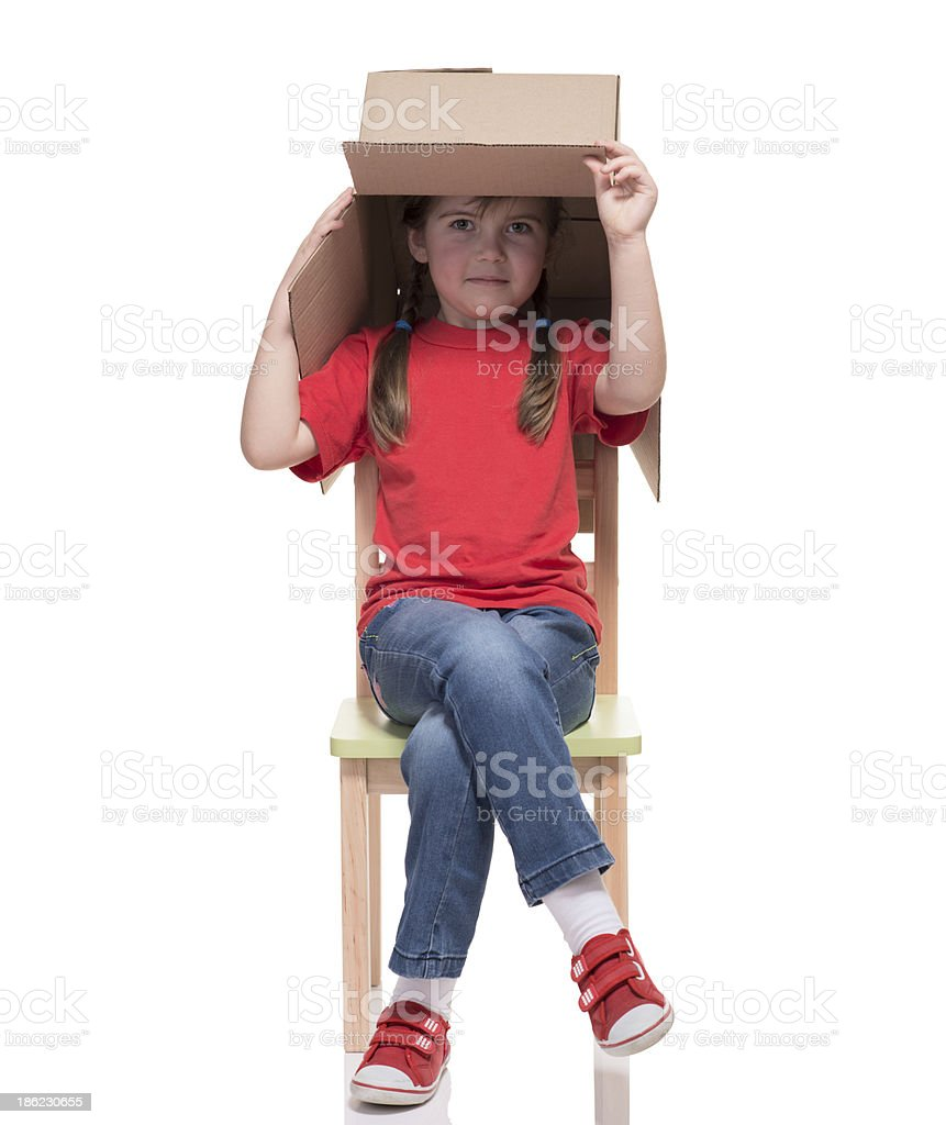 child sitting on a chair with big box covered head royalty-free stock photo