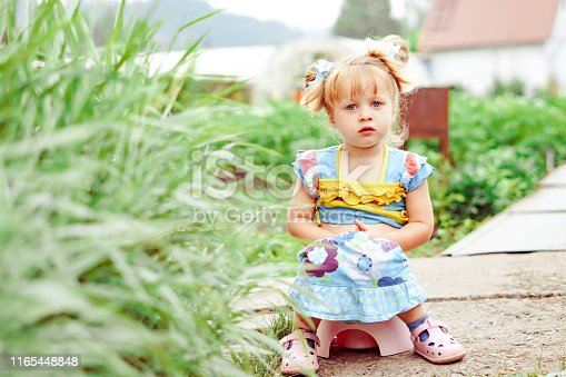 istock child sitting on a pot in nature 1165448848