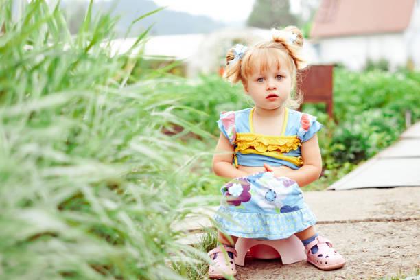 Kind sitzt auf einem Topf in der Natur – Foto