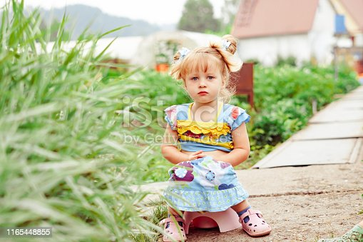 istock child sitting on a pot in nature 1165448855
