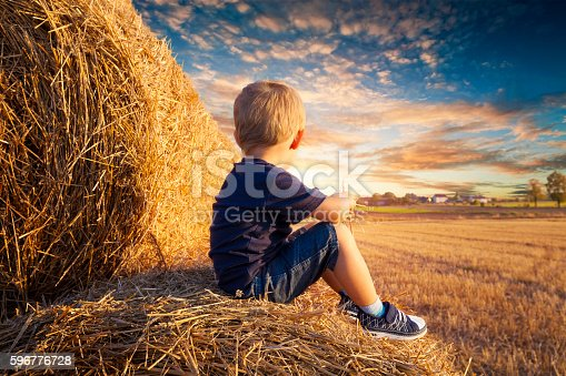 Baby sitting on bales of straw and looks up into the sunset