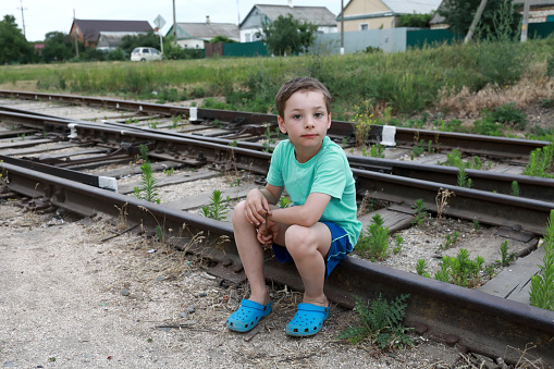 Child Sitting On Railway Tracks Stock Photo - Download Image Now - iStock