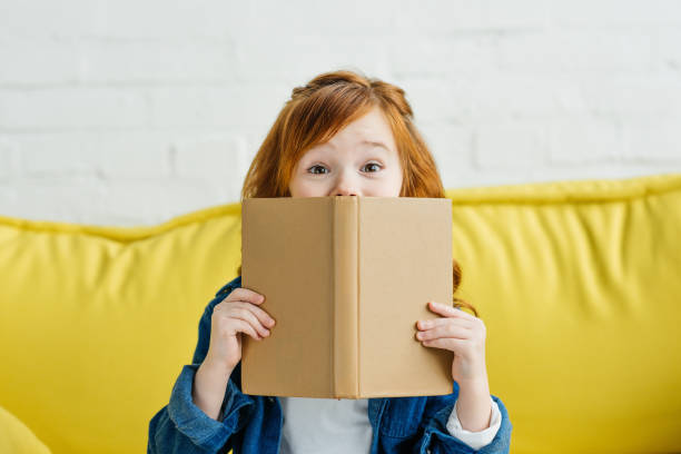 child sitting on sofa and holding book in front of her face - child stock photos and pictures