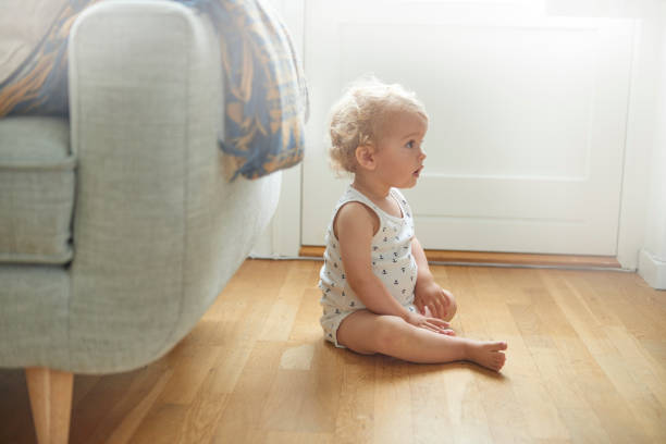 child sittinhg on floor in profile - sitting on floor stock photos and pictures