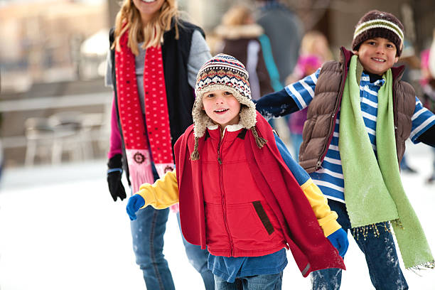 Child skates with his family a family spends the day ice-skating outdoors ice skating stock pictures, royalty-free photos & images