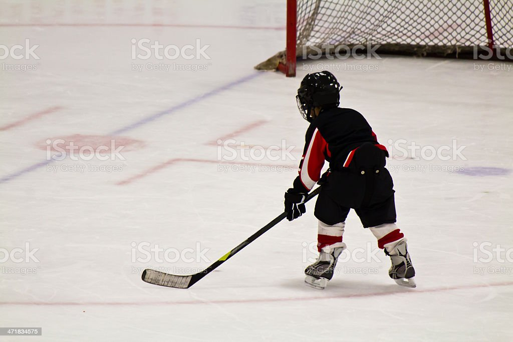 Child skating and playing hockey in an arena royalty-free stock photo