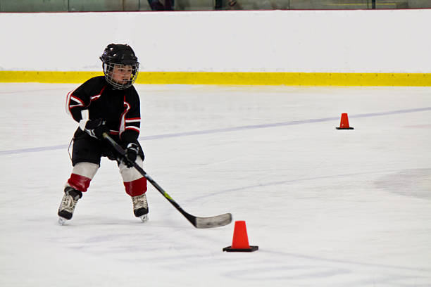 Child skating and playing hockey in an arena stock photo