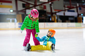 Child skating on indoor ice rink. Kids skate. Active family sport during winter vacation and cold season. Little girl and boy in colorful wear training or learning ice skating. School sport clubs