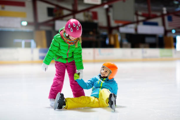 Child skating on indoor ice rink. Kids skate. Child skating on indoor ice rink. Kids skate. Active family sport during winter vacation and cold season. Little girl and boy in colorful wear training or learning ice skating. School sport clubs ice skating stock pictures, royalty-free photos & images