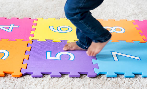 Child skipping on a numbered mat stock photo