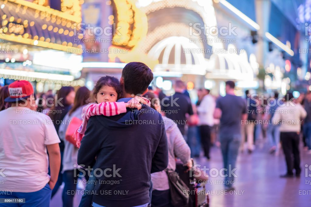 A child sleep in her father's arms at Fremont Street Experience, downtown Las Vegas stock photo