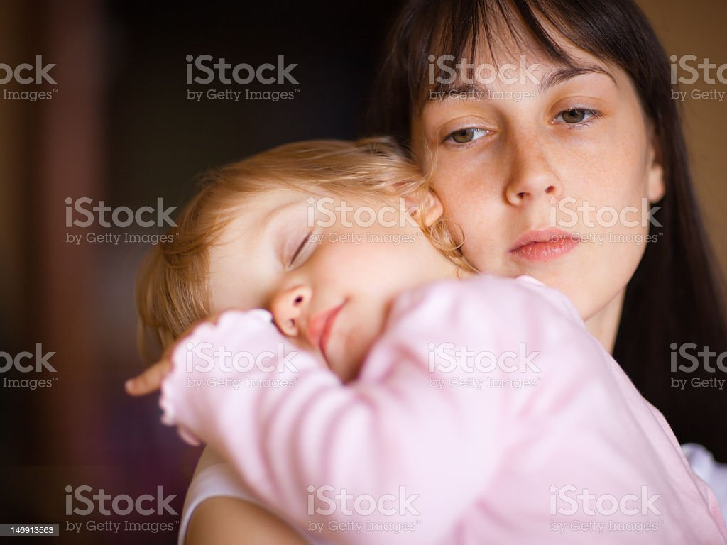 Child sleeping on mother's shoulder stock photo