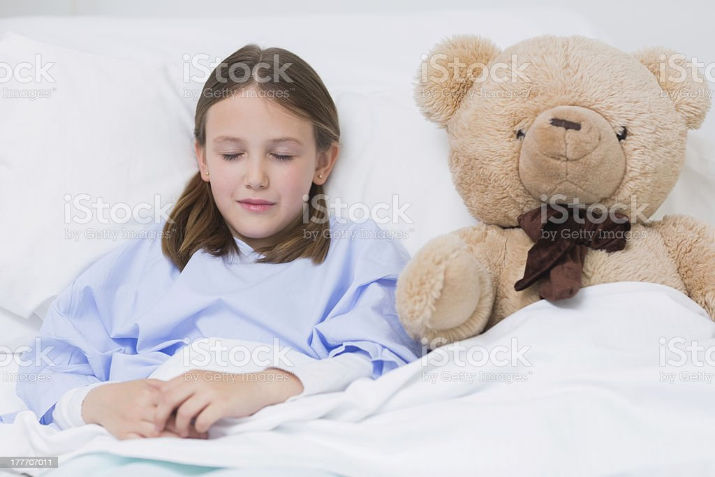 Child sleeping with a teddy bear while lying in bed royalty-free stock photo
