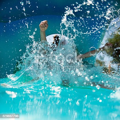 Little boy sliding in water park. Actually only his little hands visible as he splashes into water.