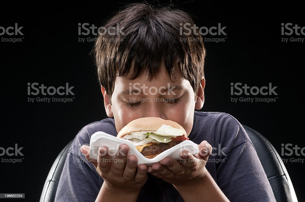 Child smelling a hamburger royalty-free stock photo