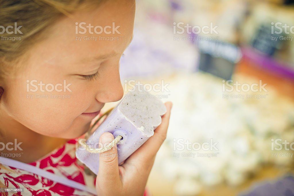 Child sniffing soap at a farmer's market in Provenve royalty-free stock photo