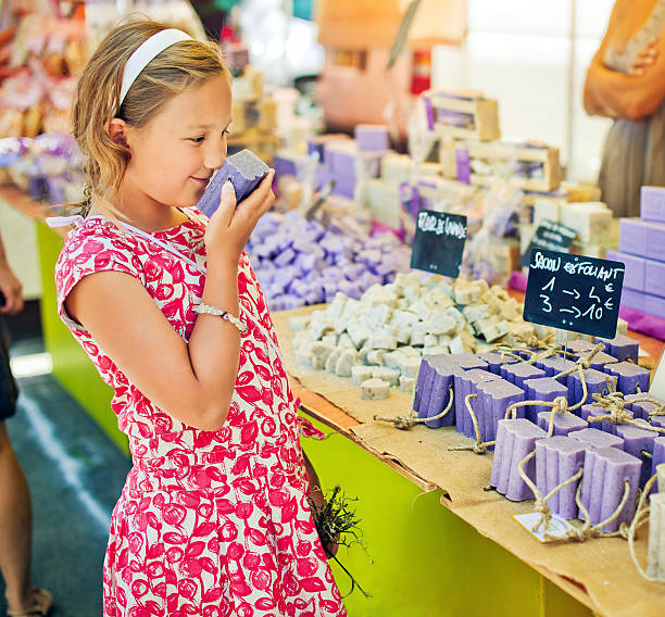 Child sniffing soap at a farmer's market in Provenve stock photo