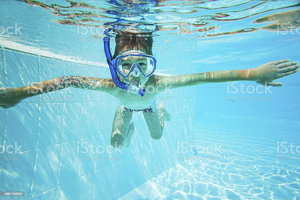 Child snorkeling in swimming pool stock photo