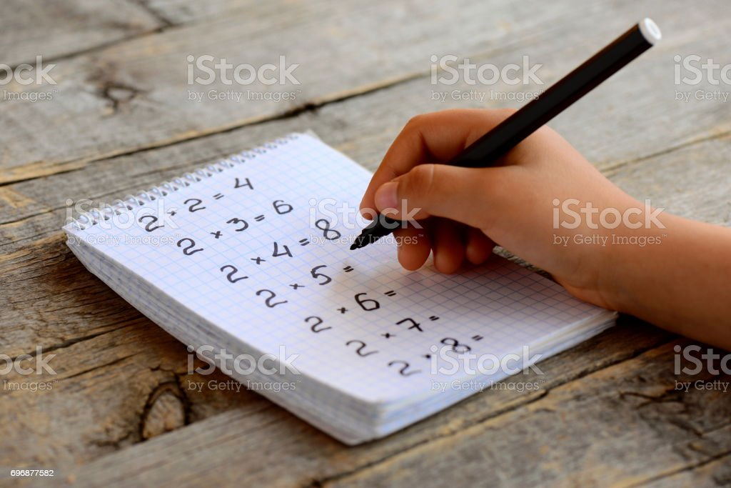 Child solves mathematics examples. Child holds a black marker in his hand. Notebook sheet with multiplication table examples. Studying a multiplication table concept stock photo