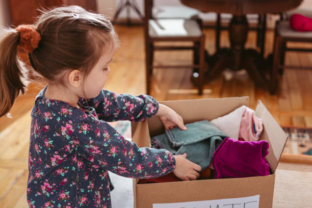 Child sorting clothes for donation Child sorting clothes for donation clothes in box stock pictures, royalty-free photos & images