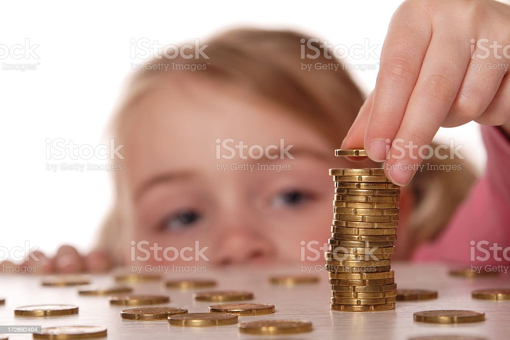 A child stacking coins on a table royalty-free stock photo