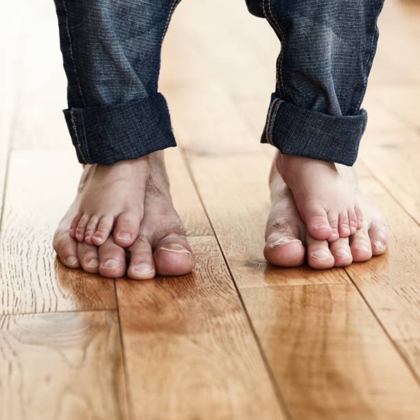 child standing barefoot on his father's feet - take care of your jeans imagens e fotografias de stock