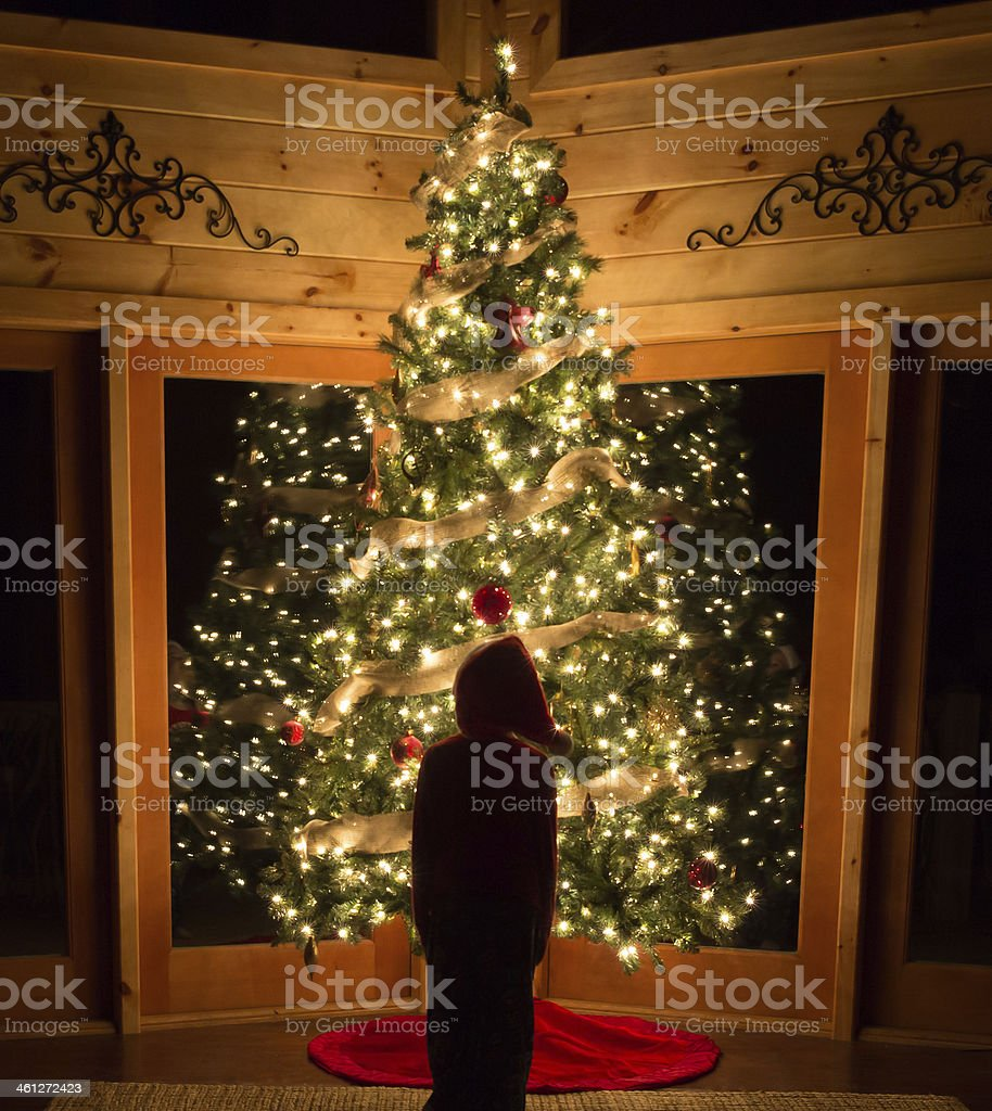 Child standing in front of illuminated Christmas tree stock photo