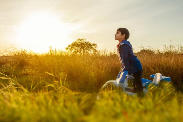 Kind, das mitten auf dem Land steht, in seinem Spielzeugauto schaut weg auf den Weg – Foto