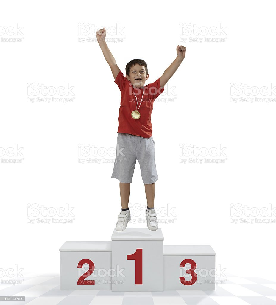 Child standing on a place podium in first place cheering stock photo