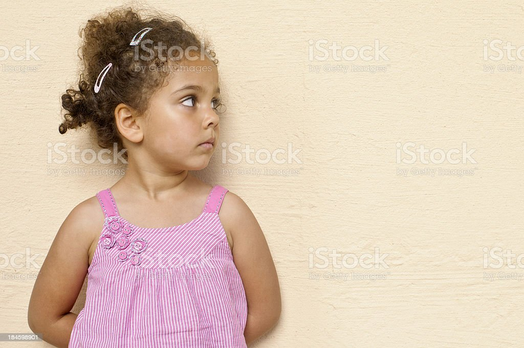 Child Standing Up Against Wall with Hands Behind Her Back stock photo