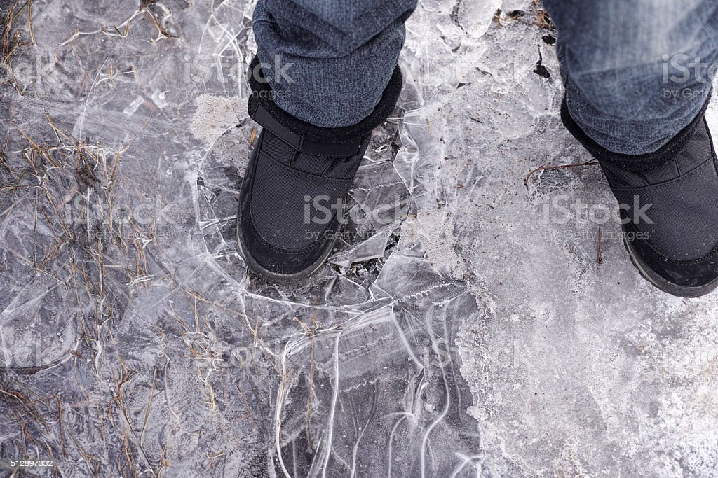 Child steps on frozen puddle with thin ice stock photo