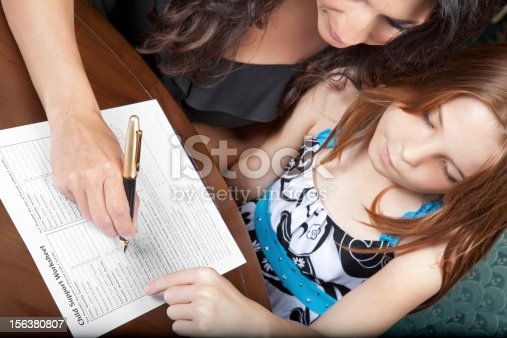 Daughter watching mom fill out child support forms