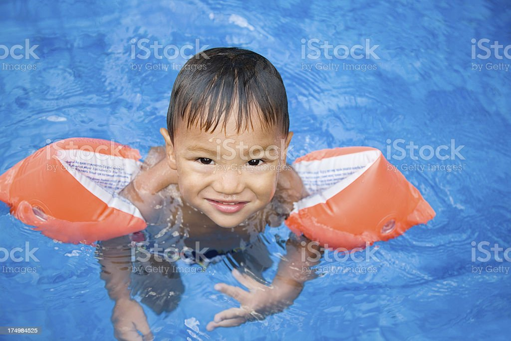 Child swimming in pool stock photo