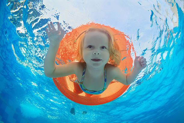 kind schwimmen im schwimmbad mit aufblasbaren u-bahn orange - pool rund stock-fotos und bilder