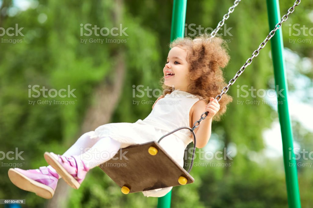 Child swinging on a swing at  playground in the park. stock photo