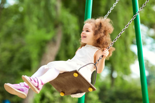 Enfant se balancer sur une balançoire au terrain de jeux dans le parc. - Photo