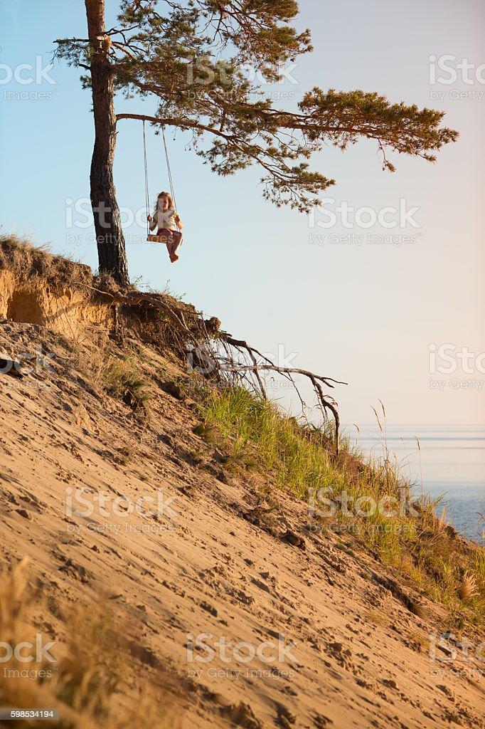 Child swinging on seesaw above a sea sunrise photo libre de droits