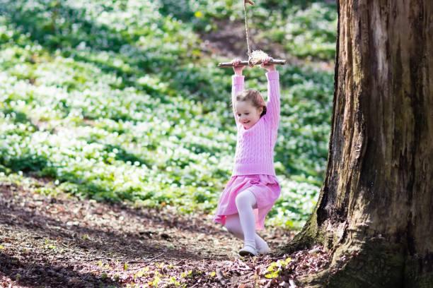 kind schwingt auf baumseilschaukel - sommerfest kindergarten stock-fotos und bilder