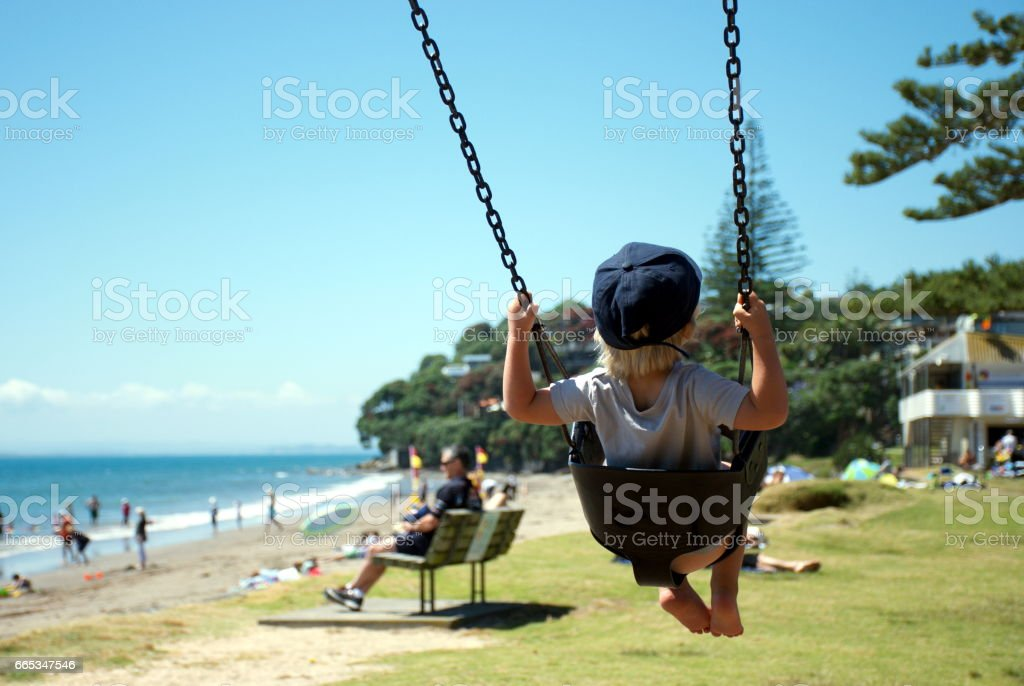 A Child swings on a Swing at a Beach Park in Summer stock photo