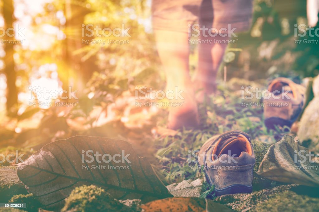 Child take off shoes. Child's foot learns to walk with sunlight. stock photo