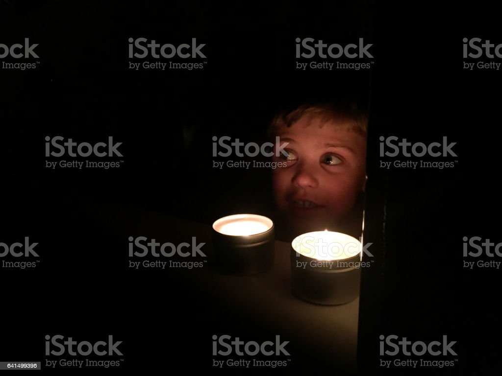 Child taking a bath with two candles burning stock photo