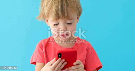 istock Child tapping cell phone screen, interest in modern technology 1141454752