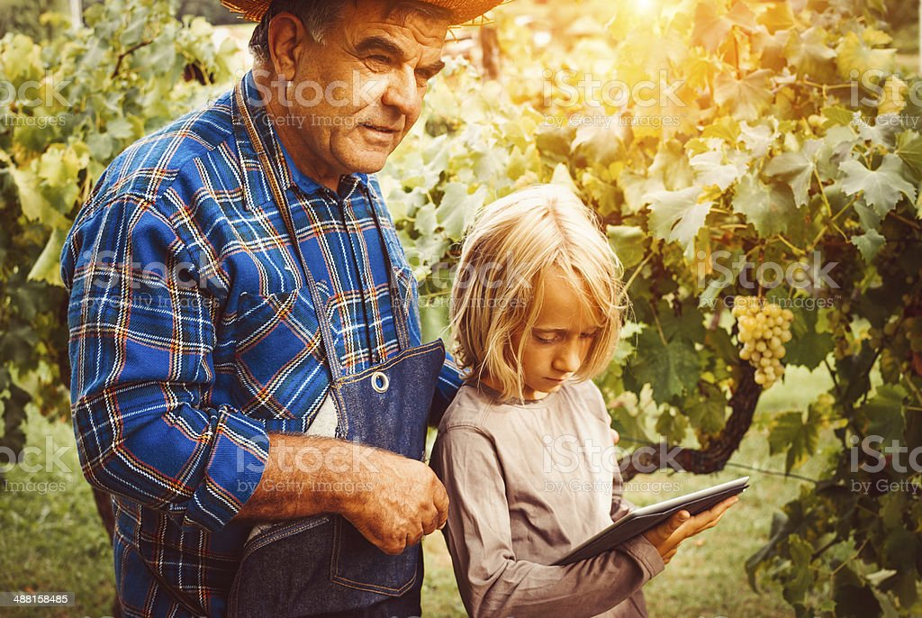 Child teaches to a farmer man using tablet pc stock photo