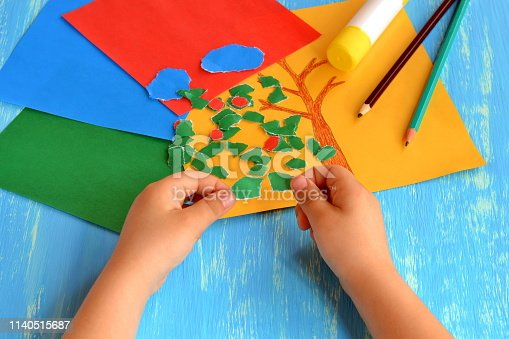 istock Child tears a red paper into small pieces. Child holds red paper pieces in his hands. Kindergarten art lesson. Set of color paper, pencils, glue stick on wooden background. Fun paper crafts for kids 1140515687