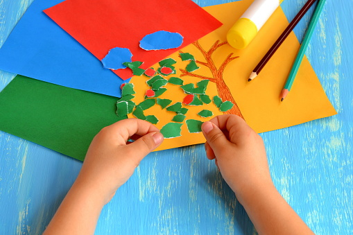 Child tears a red paper into small pieces. Child holds red paper pieces in his hands. Kindergarten art lesson. Set of color paper, pencils, glue stick on wooden background. Fun paper crafts for kids