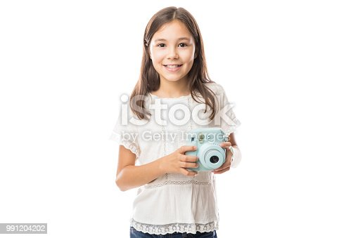 Smiling young girl holding photo camera and taking pictures isolated on white