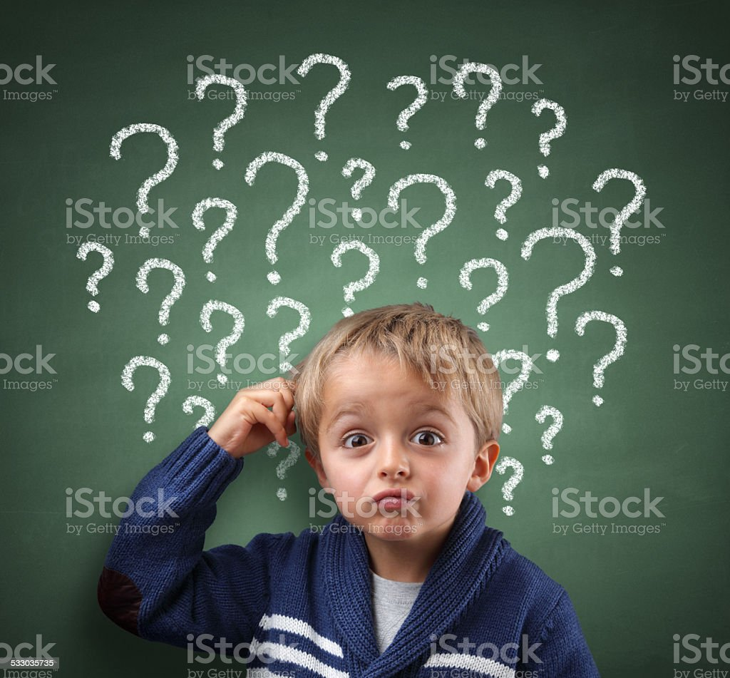 Child thinking with question mark on blackboard stock photo