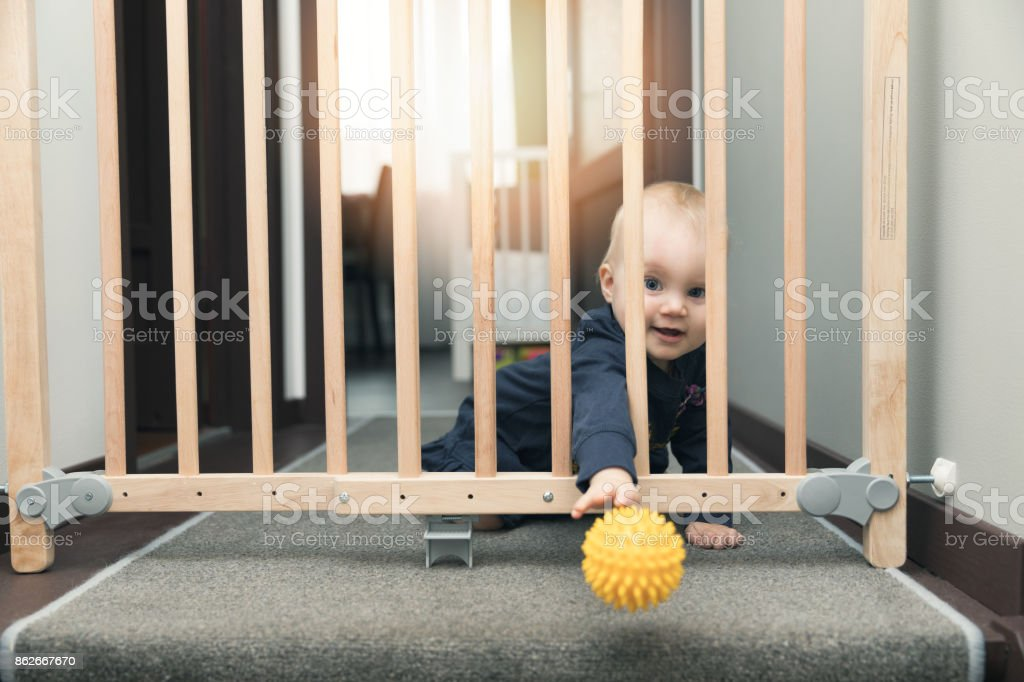 child throwing ball away through safety gates in front of stairs stock photo