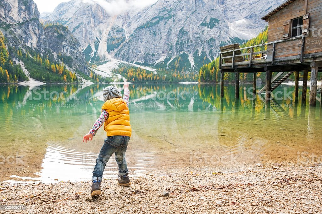 Child throwing stones on lake braies, italy. rear view stock photo